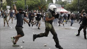 A protester chases a policeman with a wooden stick during violent protests around Syntagma square in Athens June 29, 2011.