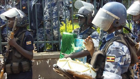 Police in Kampala, Uganda, walk away with a birthday cake for President Museveni