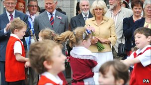 The Prince of Wales and the Duchess of Cornwall watch folk dancing by children from Ysgol Rhys Prichard primary school at Llandovery railway station