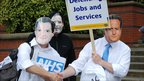 Protesters wearing Nick Clegg and David Cameron masks
