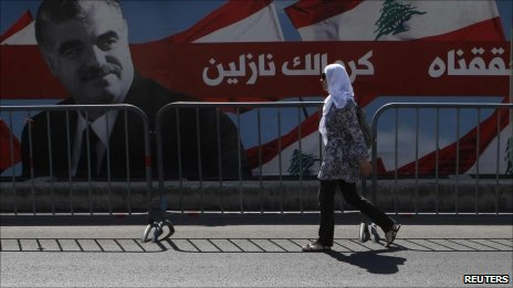 Beirut - Woman walks in front of Hariri poster. 30 June 2011