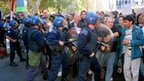 State workers are pushed by riot police in San Juan, Argentina, April 2002.