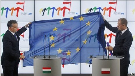 Hungary PM Viktor Orban, left, hands EU flag to Poland's PM Donald Tusk, 1 July 11