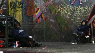 Homeless men sitting in front of mural
