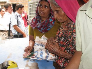 Women buying staples from the government shop using their smart cards