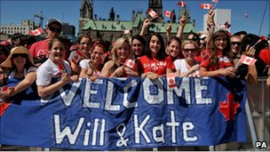 Well-wishers stand in front of a Welcome Wills and Kate banner