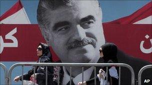 Women pass by a giant portrait of former Lebanese Prime Minister Rafik Hariri near his grave, Beirut, Lebanon, 30 June 2011