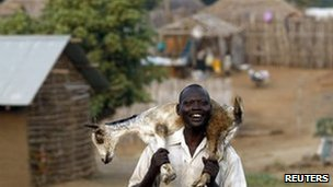 A man smiles as he carries a goat on his shoulders to sell in a market in Juba (2 July).