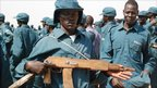 Police recruit holding a wooden gun