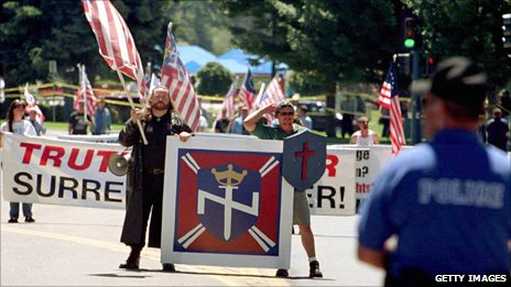 Members of the white supremacist group Aryan Nations march under the surveillance of police in Coeur d'Alene, Idaho