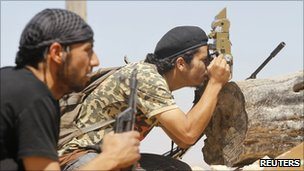 Near Kikla, a rebel fighter uses an optical sight from a captured government