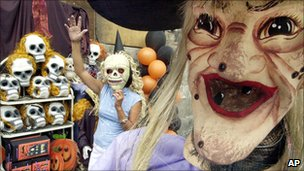 A vendor selling Halloween items waves to passing customers in Manila