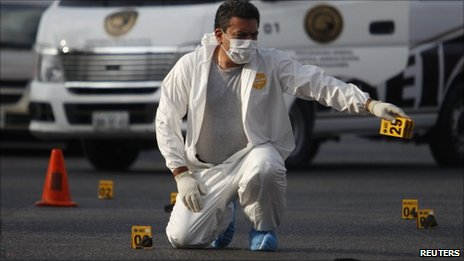 Member of a forensic team gives instructions to his colleagues at a crime scene in San Nicolas de los Garza, neighbouring Monterrey, 5 July 5, 2011.