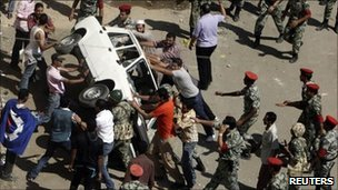 Protesters overturn a police car in front of the courthouse in Suez, 6 July