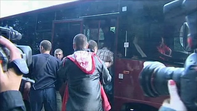 Protester being pushed onto a bus