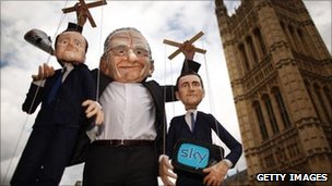 Puppets representing Prime Minister David Cameron (L) and Culture Secretary Jeremy Hunt (R) are held aloft by a protester dressed as Rupert Murdoch 