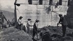Workers clearing brush around a large stone wall