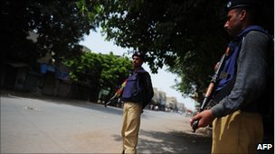 Pakistani policemen stand guard in a deserted street in a western neighbourhood affected by the political violence in Karachi on 7 July 2011