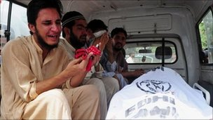 Relatives of a person killed by political violence mourn over the body inside an ambulance at the Jinnah Postgraduate Medical Centre in Karachi on 6 July 2011