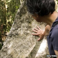 Woman examines engraving on rock, on the Pic de Bugarach