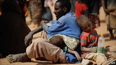 Somali man who fled violence and drought in Somalia with his family sits on the ground outside a food distribution point in the Dadaab refugee camp in northeastern Kenya on 5 July 2011