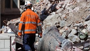 Urban Search and Rescue workers walk past piles of debris as they enter the Christchurch Cathedral in Cathedral Square after it was severely damaged in the recent earthquake, on 5 March 2011