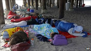 People sleeping under a pier before the shuttle lift-off