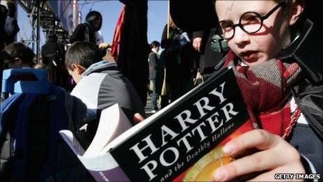 Child holds a copy of Harry Potter