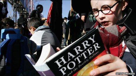 Child holds a copy of Harry Potter