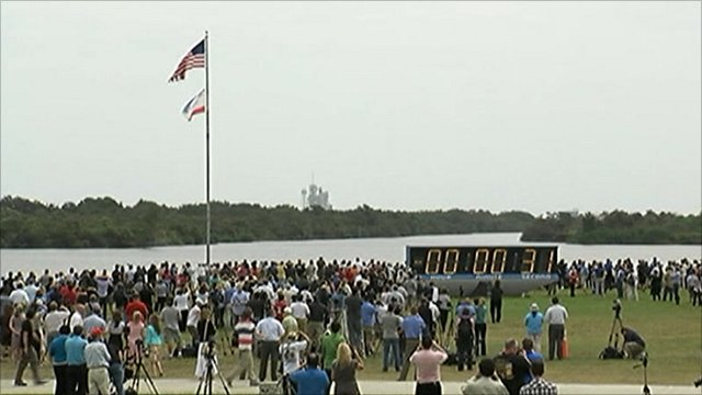 Spectators watch as the countdown clock freezes at 31 seconds to launch