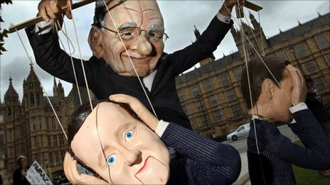 A demonstrator dressed in a Rupert Murdoch mask controls puppets of British Prime Minister David Cameron