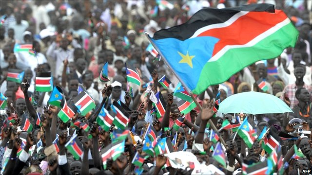 Crowd of South Sudanese people waving their national flag to celebrate independence