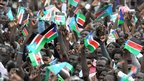 South Sudanese watch a giant flag being raised during a ceremony in the capital Juba on 9 July 2011 to celebrate South Sudan's independence from Sudan.