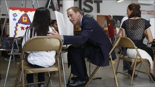 Prince William and his wife, Kate, Duchess of Cambridge, painting pictures with a child
