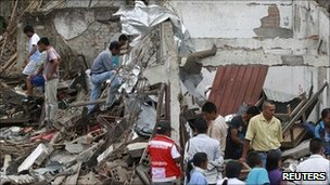 People surround a house that was damaged after being hit by a bus that detonated in Toribio, in Cauca province, 9 July 2011
