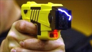 Police officer demonstrates a Taser gun