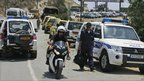 Rescuers and Police cars gather at the entrance of the Evangelos Florakis naval base in Mari, Cyprus, 11 July.