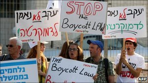 Israeli demonstrators hold up signs calling for a halt to the boycott bill