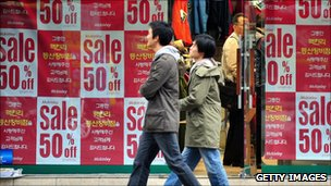 Shoppers walking outside a store with sale sign