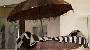 A wooden canoe and umbrella in