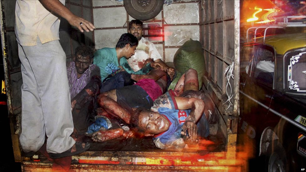Injured victims of a bomb explosion are loaded onto a truck to be taken to hospital in the Zaveri Bazaar area of Mumbai
