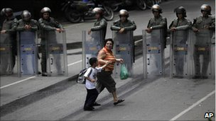 An unidentified woman passes with a child near a line of National Guard soldiers outside El Rodeo II prison in Guatire, Venezuela, Tuesday June 21, 2011.