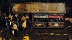 Police inspect a bus stop damaged by the bomb in the Dadar area of Mumbai