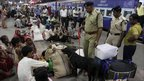 Police with sniffer dogs inspect travellers at a railway station in Ahmadabad, India - 13 July 2011