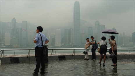 Tourist takes pictures against Hong Kong's harbour on July 12.