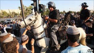 A mounted police officer is surrounded by religious Jewish Israelis.