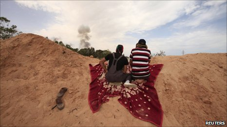 Young men peer over sandbank on front line near Misrata