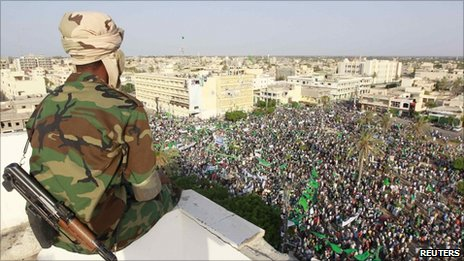 A Libyan soldier watches as supporters of Libya's leader Muammar Gaddafi take part in a rally in the town of Zawiya, 16 July 2011 - photo taken on government guided tour