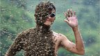 """Beekeeper Lu Kongjiang, 20, stands with bees covering his body on a weighing scale during a """"bee-attracting"""" competition against fellow beekeeper Wang Dalin in Shaoyang, Hunan province July 16, 2011"""