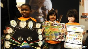 School children hold birthday cards during a symbolic handover on 17 July 2011 at the Nelson Mandela Foundation in Johannesburg